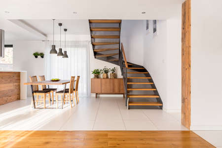 Open space with industrial half-landing stairs and wooden dining area Archivio Fotografico
