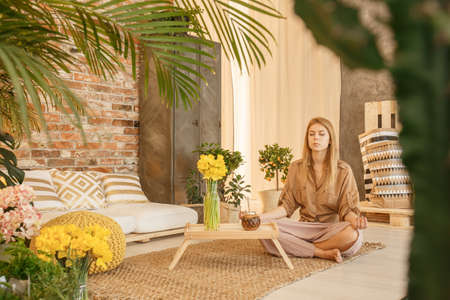 Young woman relaxing in cozy loft with botanic decor Stock Photo