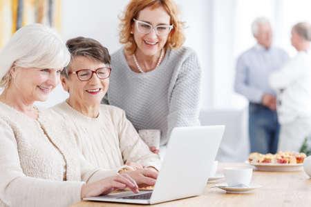 Three modern happy grandmothers using new technology laptop