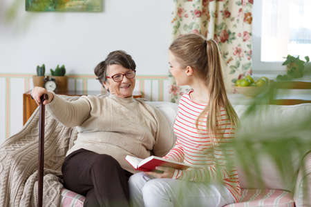 Happy grandma talking to her young granddaughter Imagens