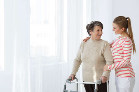 Girl with her arm around her grandma with a walker