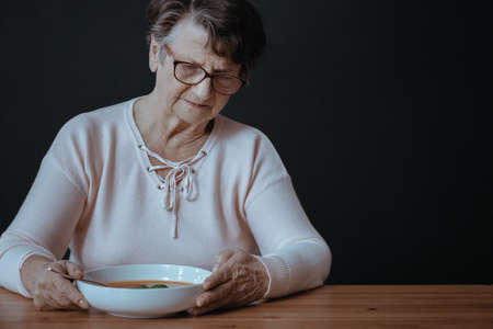 Older lady during dinner suffering from lack of appetite Foto de archivo