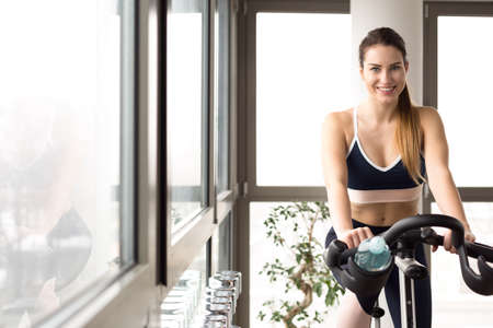 penthouse: Beautiful woman on exercise bike in her private gym Stock Photo