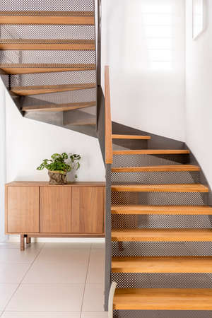 Industrial metal and wooden half-landing stairs in simple family home 版權商用圖片