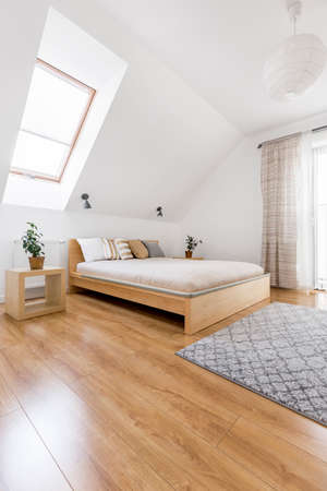 Comfortable king size wooden bed in cozy minimalist attic bedroom