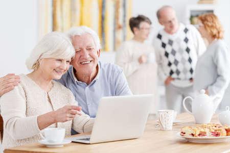 Felice coppia di anziani parlando con i loro figli in linea