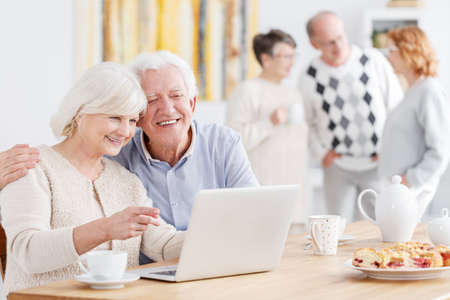 Happy elderly couple talking with their children online Stock Photo