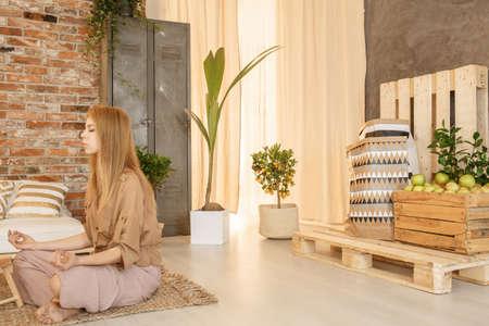 居心地の良い木造のリビング ルームで彼女の禅の地域の女性を瞑想 写真素材