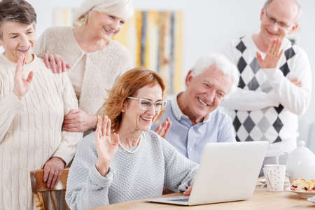 third age: Elderly happy people talking online using laptop with old friend Stock Photo