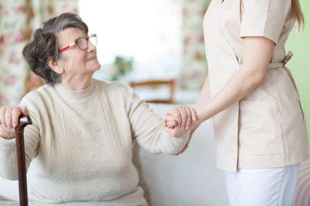 Senior lady with walking stick sitting and holding nurses hand Stock Photo