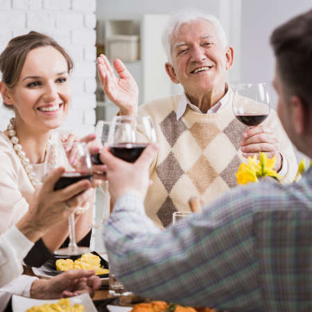 Happy caucasian family making a toast with red wine during birthday