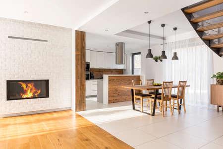 Armonioso espacio abierto con chimenea, cocina y comedor Foto de archivo