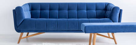 Blue comfortable sofa and small table in white living room