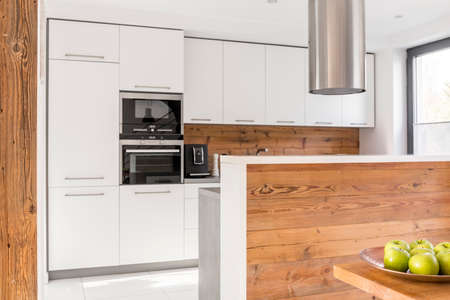 Scandinavian design of modern kitchen with white cabinets and wooden panels 版權商用圖片