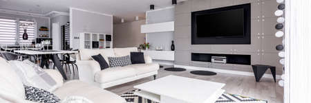 Elegant, black and white relax zone with home cinema system Фото со стока
