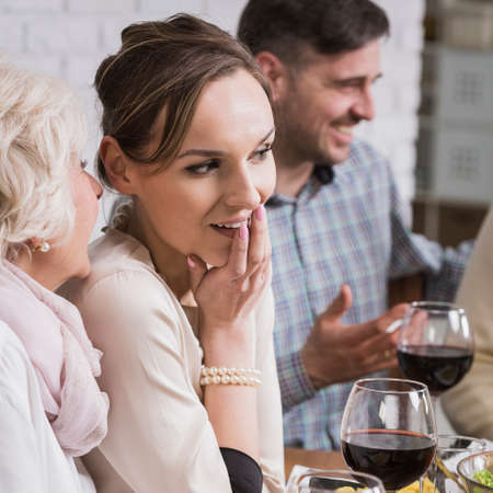 rumour: Mature woman whispering to young woman, sitting beside table during family dinner Stock Photo
