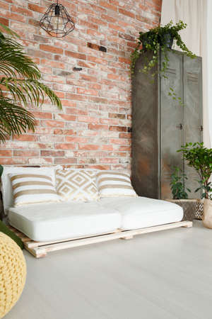 White comfortable sofa by the red brick wall in spacious room