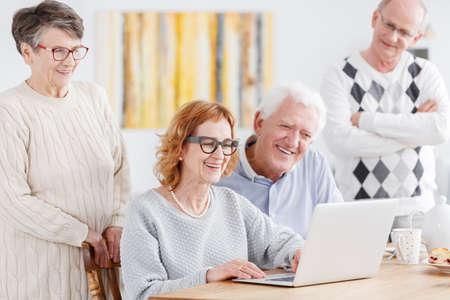笑顔のグループにラップトップ上の古い写真を見ている人が高齢者 写真素材