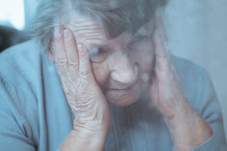 Sad lonely senior lady suffering from migraine Stock Photo