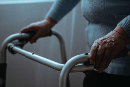 Solitaria dama senior de pie con un andador Foto de archivo - 81873684