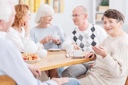 特別養護老人ホームでコーヒーを飲みながら高齢者のグループ