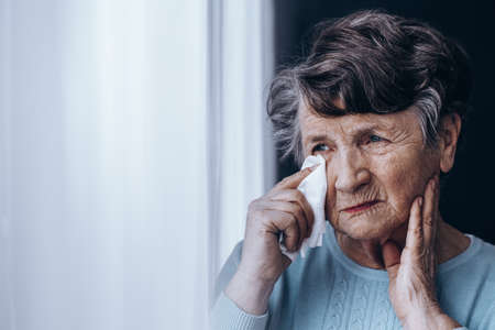 teary: Sad elderly woman with teary eyes looking through the window