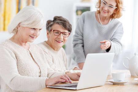 Oudere slimme vrouw die nieuwe laptop op een vergadering met behulp van Stockfoto