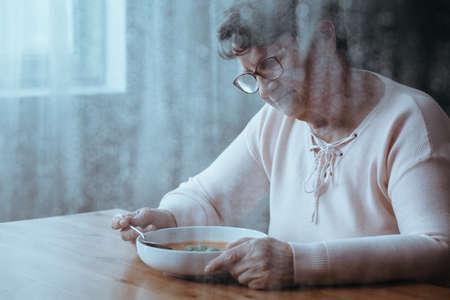 혼자 토마토 수프를 먹고 슬픈 아줌마 스톡 콘텐츠