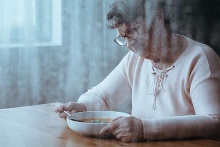 Sad older woman eating tomato soup alone