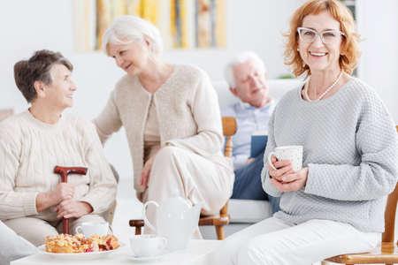 シニア クラブでお茶を飲む優雅な幸せな年上の女性