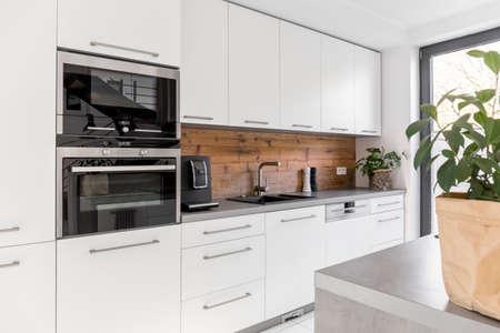 バランスのとれたキッチン ワークトップの白いキャビネット グレーと自然なアクセント