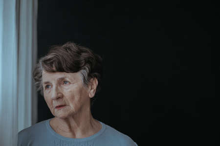 Sad senior lady alone in the dark room