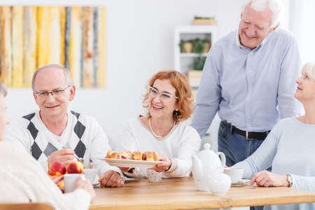 かなり年上の女性が彼女の年長の友人にケーキを提供