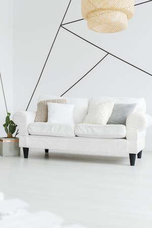Grote houten lampenkap hangt boven een witte comfortabele bank