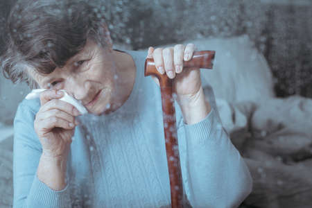 Sad senior lady wiping her eyes with a tissue Stock Photo