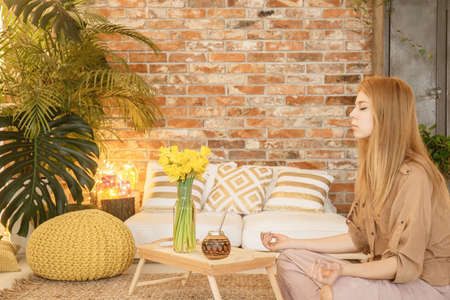Young girl meditating in her cozy living room full of plants