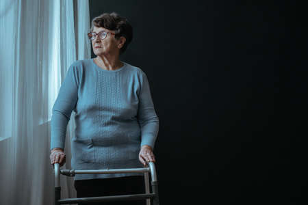 Older woman standing with a walker by the window