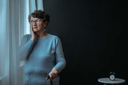 headaches: Worried senior lady looking through the window