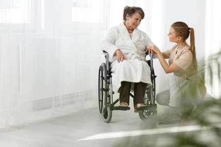 Hogere dame in een rolstoel die bij haar verpleegster glimlacht Stockfoto