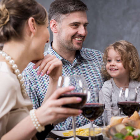 Father sitting with smiling little daughter and family at the table and drinking wine