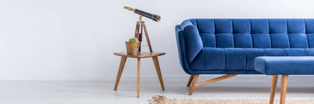 Blue sofa and table with plant and telescope in white room