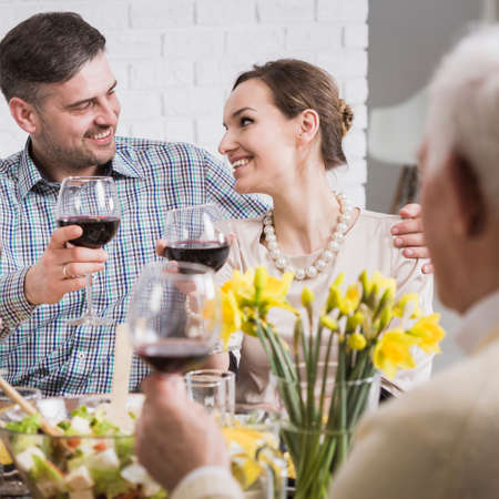 Young happy couple and their parents celebrating anniversary with red wine and festive dinner