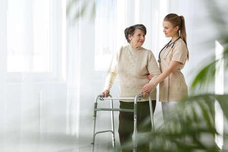 Jonge verpleegster die haar hogere damepatiënt behandelt