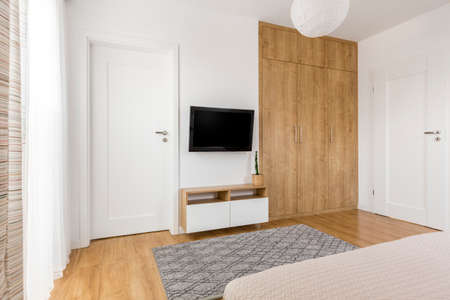 Practical and minimalist bedroom TV wall with wooden spacious wardrobe