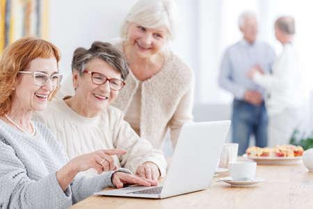 写真を見てのラップトップを使用して 3 つの年配の女性