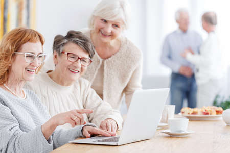 Three older women using laptop to watch photos