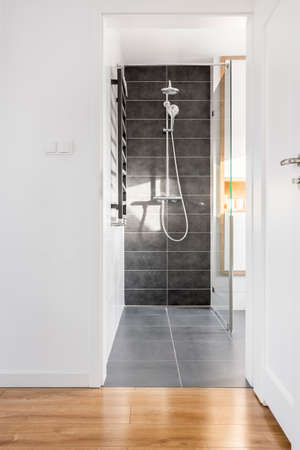 Modern functional light bathroom with large grey shower tiles 版權商用圖片