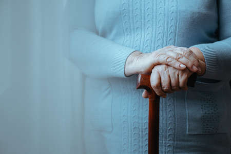Oudere dame die zich met een houten wandelstok bevindt Stockfoto