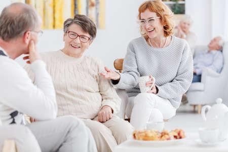シニアの幸せな女性と老人のお茶会でおしゃべり