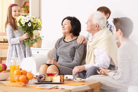 Lovely granddaughter giving beautiful bouquet of flowers to happy grandparents 스톡 콘텐츠